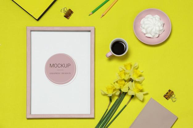 Modellfotorahmen auf dem gelben hintergrund mit blumen, kaffee, kuchen