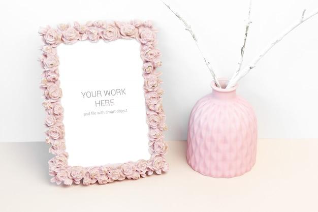 Modellfotorahmen mit rosarosenblume und rosa vase