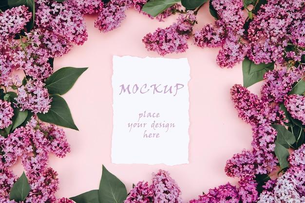 Modellpostkarten auf einem rosa hintergrund mit zweigen des blühenden flieders