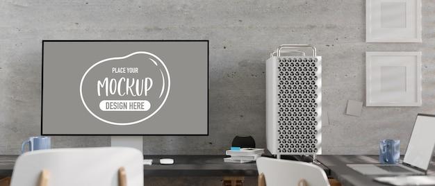 Modern-loft-büroraum mit desktop-computermodell mit leerem bildschirm, laptop, büchern, tasse, stühlen, bilderrahmen und bürobedarf. 3d-rendering, 3d-darstellung
