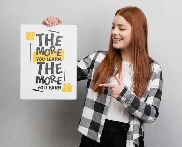 Moderne frau, die auf modell zeigt