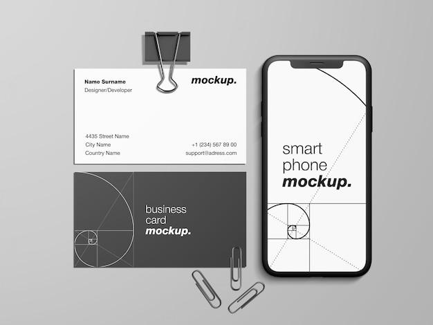 Moderne visitenkarten und smartphone-modellvorlage mit büroklammern und papierblinder