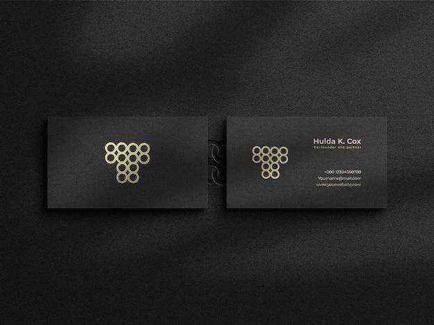 Modernes luxus-visitenkartenmodell mit goldfolieneffekt auf dunklem hintergrund