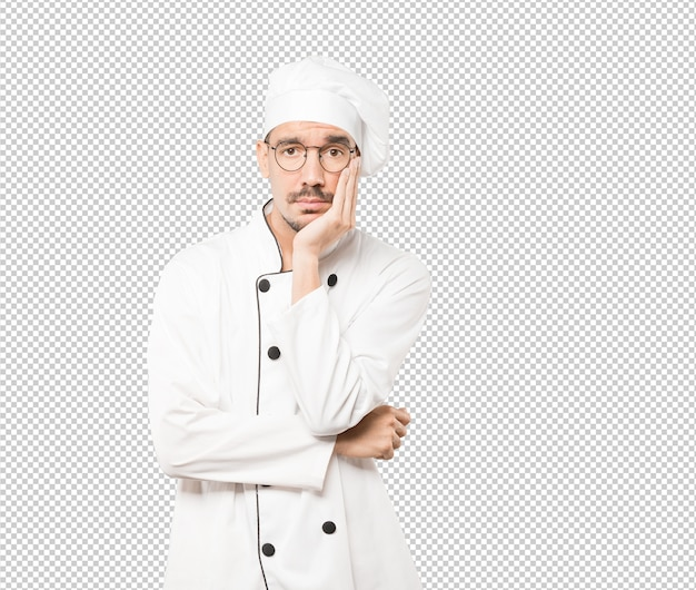 Müder junger koch, der eine geste der langeweile tut
