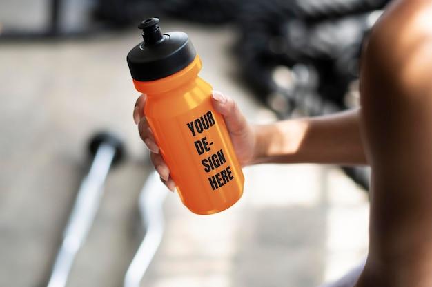 Muskulöser mann, der ein orangefarbenes wasserflaschenmodell hält