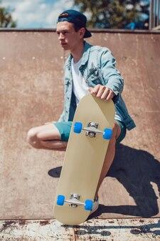 Nahaufnahme auf young man holding skateboard mockup