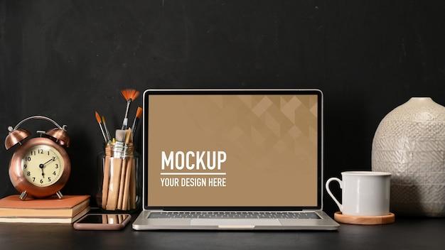 Nahaufnahme des arbeitsbereichs mit laptop-modell, kaffeetasse und zubehör