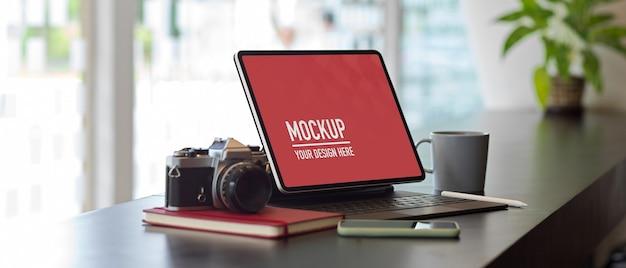 Nahaufnahme des arbeitstisches mit digitalem tablet, kamera, briefpapier und zubehör des modells