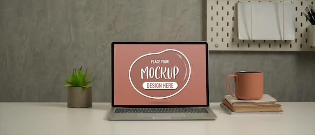Nahaufnahme des arbeitstisches mit mock-up-laptop, notebooks, becher und dekoration im loft-wohnzimmer