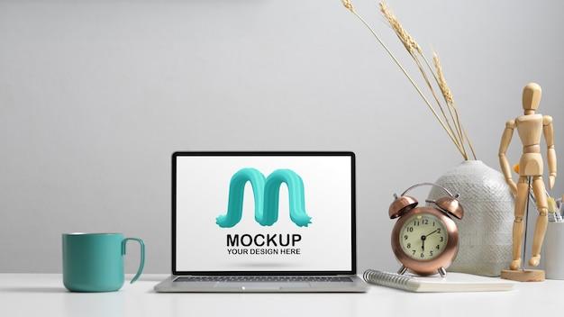 Nahaufnahme des arbeitstisches mit modell laptop, uhr, notizbuch, becher und dekorationen im home office