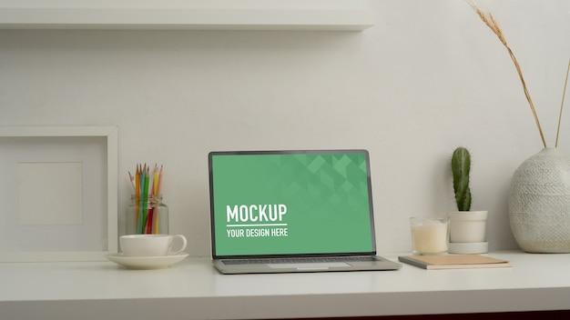 Nahaufnahme des home-office-schreibtisches mit mock-up-laptop, briefpapier und dekorationen