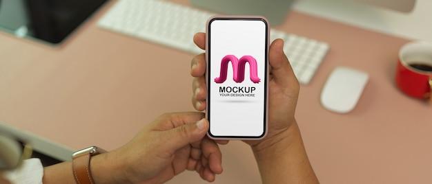 Nahaufnahme des mannes, der modell-smartphone auf modernem bürotisch hält