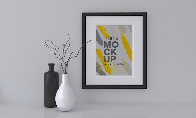 Nahaufnahme eines schwarzen rahmenmodells neben vasen auf einem grauen wandhintergrund