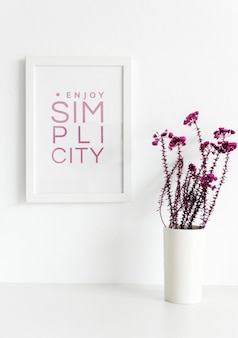 Nahaufnahme von rosa blumen in weißer vase mit fotorahmen an der wand