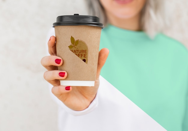 Nahaufnahmefrau mit hoodie, der kaffee trinkt