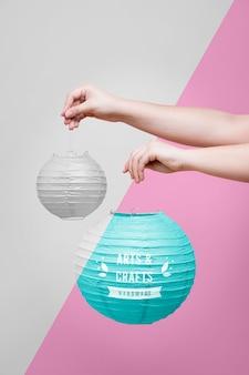 Nahaufnahmehände, die verschiedene papierlampen halten
