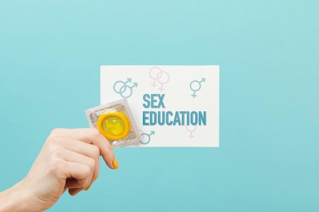 Nahaufnahmehand, die gelbes kondom hält