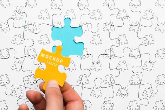 Nahaufnahmemann, der ein gelbes stück des puzzlespiels hält