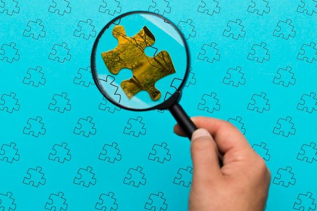 Nahaufnahmemann, der ein stück des puzzlespiels betrachtet