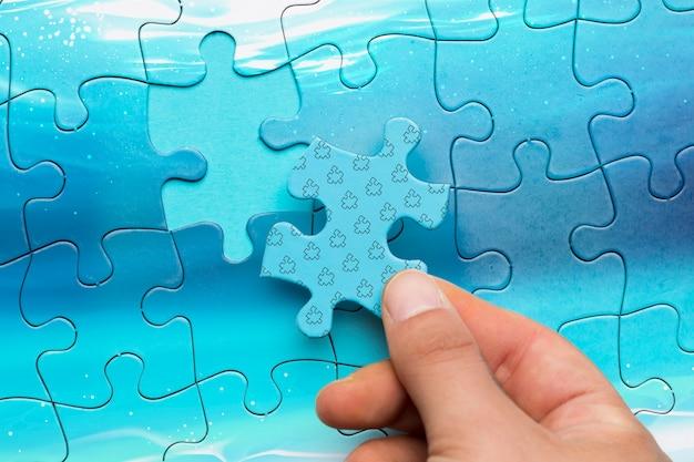 Nahaufnahmemann, der ein stück des puzzlespiels hält