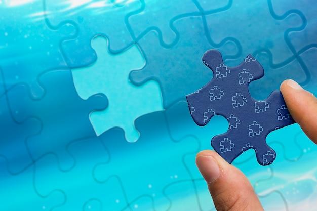 Nahaufnahmemann, der puzzlestück hält