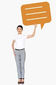 Nette asiatische frau, die ein spracheblasesymbol hält