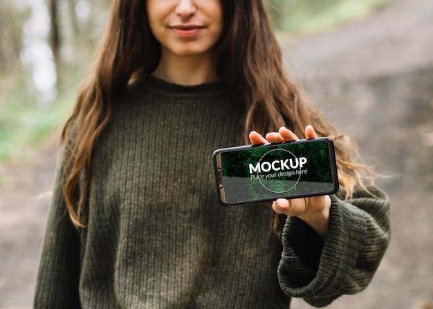 Nette frau in der natur mit smartphone-modell