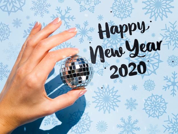 Neues jahr 2020 mit der hand, die eine weihnachtskugel anhält