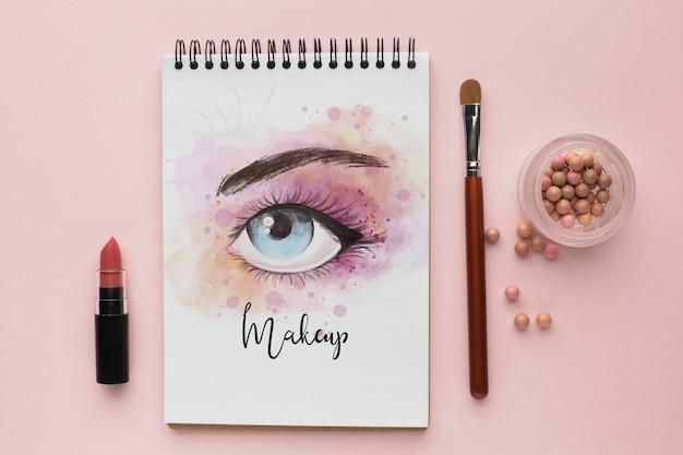 Notizbuch mit make-up für augenkonzept