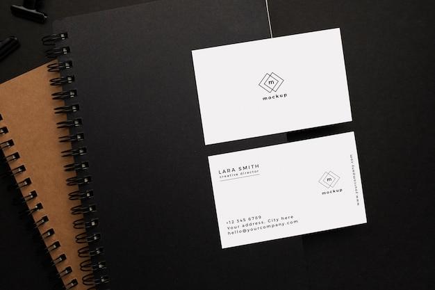 Notizbücher und visitenkartenmodell mit schwarzem element auf schwarzem hintergrund