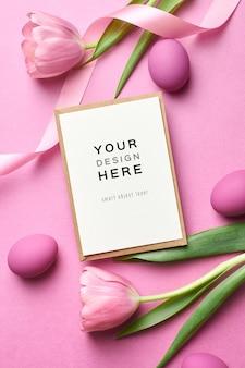 Osterferiengrußkartenmodell mit farbigen eiern und tulpen auf rosa