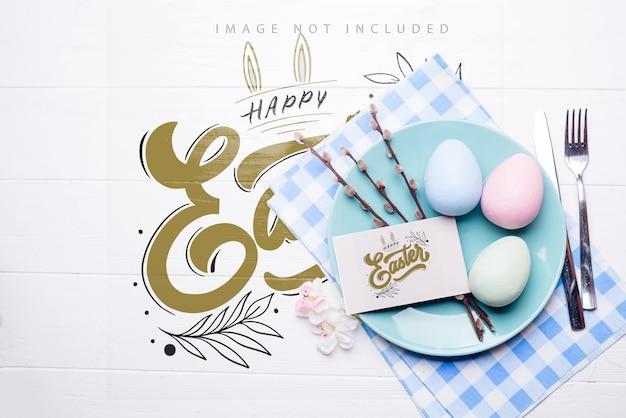 Ostertischgedeck mit eiern, besteck und serviette auf modelloberfläche,