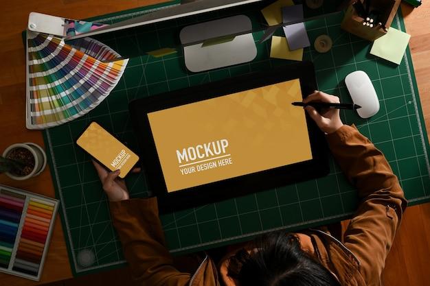 Overhead-aufnahme der grafikdesignerin, die mit mock-up-tablet und smartphone arbeitet