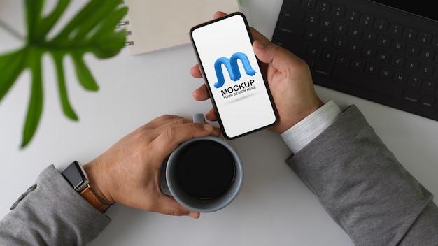 Overhead-aufnahme des männlichen unternehmers machen eine pause mit kaffee und modell smartphone