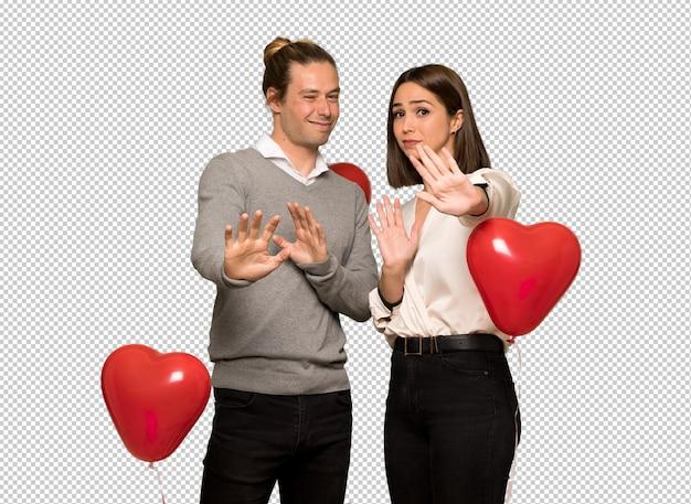 Paar am valentinstag ist ein bisschen nervös und verängstigt, die hände nach vorne ausstrecken
