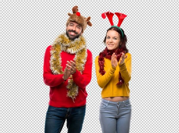 Paar gekleidet für die weihnachtsfeiertage, die nach darstellung in einer konferenz applaudieren