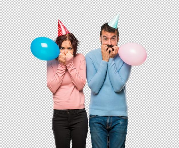Paar mit ballons und geburtstag hüte ist ein bisschen nervös und angst hände in den mund zu setzen