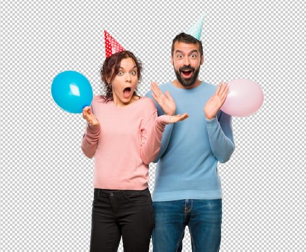 Paar mit ballons und geburtstag hüte mit überraschung ausdruck, weil nicht erwarten, was passiert ist