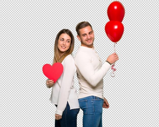 Paare am valentinstag, der ein herzsymbol und -ballone hält