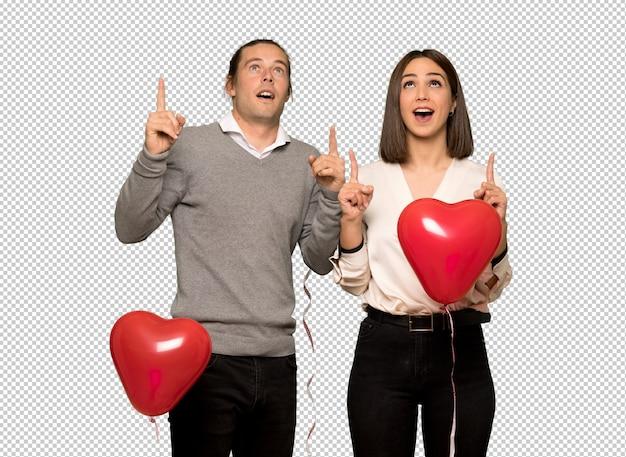 Paare am valentinstag überrascht und oben zeigend