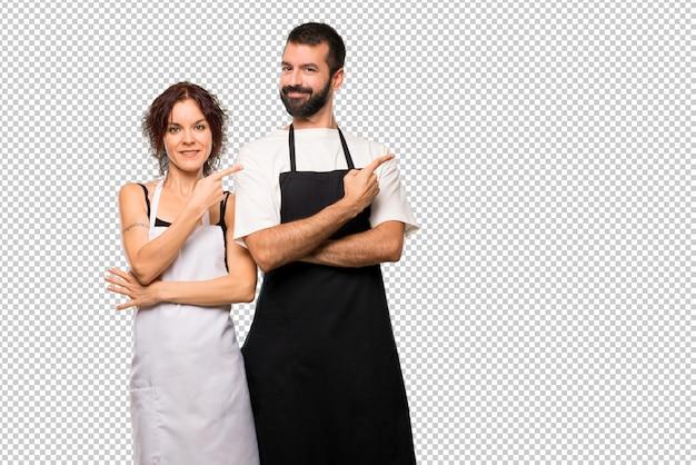 Paare der köche, die auf die seite mit einem finger zeigen, um ein produkt zu präsentieren