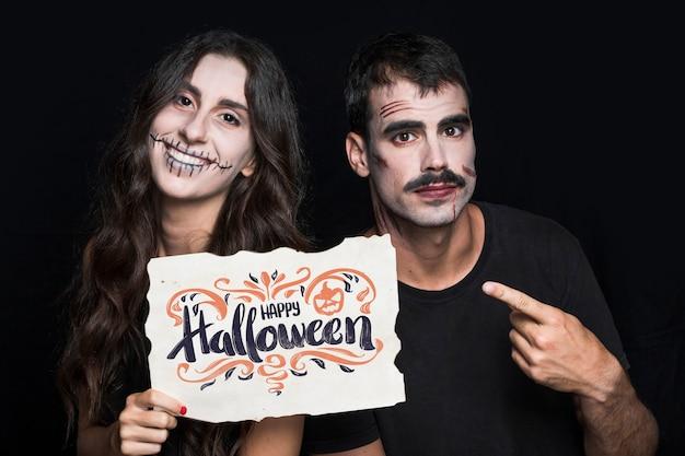 Paare, die papier mit halloween-beschriftung halten