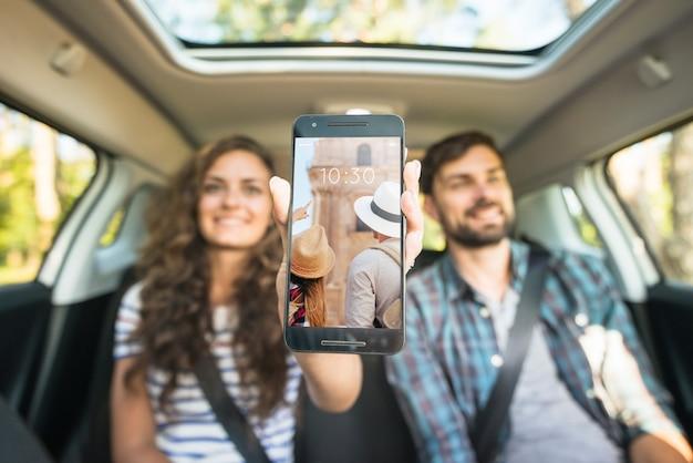 Paare im auto, das smartphonemodell zeigt