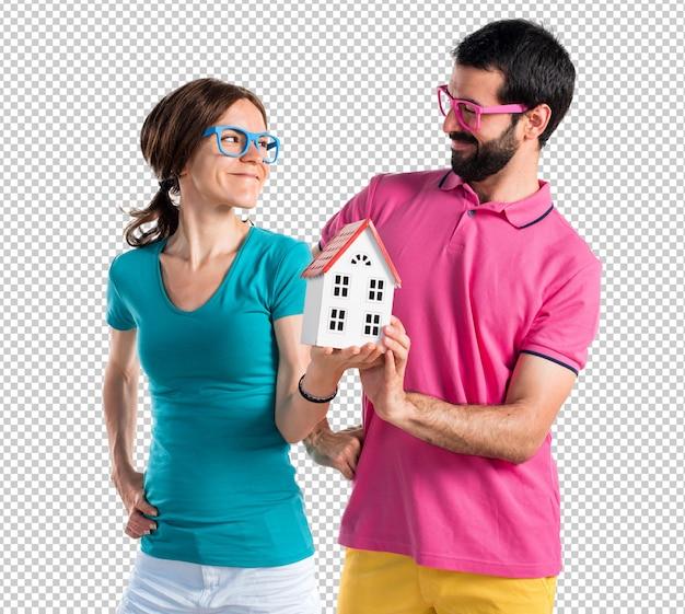 Paare in der bunten kleidung, die ein kleines haus hält