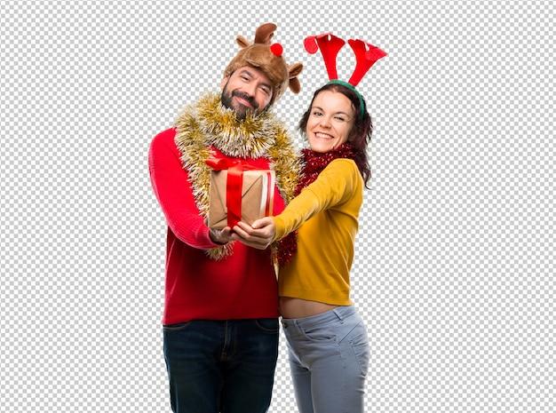 Paare kleideten oben für die weihnachtsfeiertage an, die ein geschenk halten