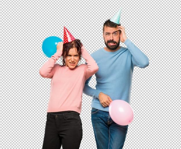 Paare mit ballonen und geburtstagshüten nimmt hände auf kopf, weil migräne hat