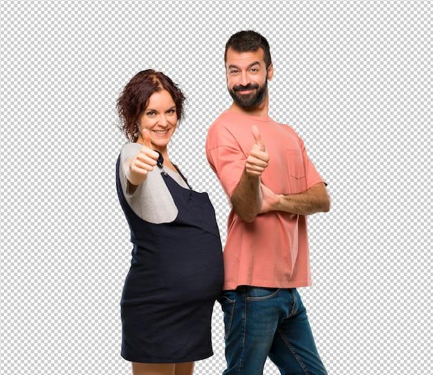 Paare mit dem geben der schwangeren frau daumen up geste und dem lächeln