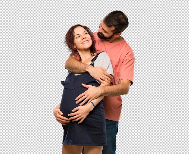 Paare mit dem umarmen der schwangeren frau