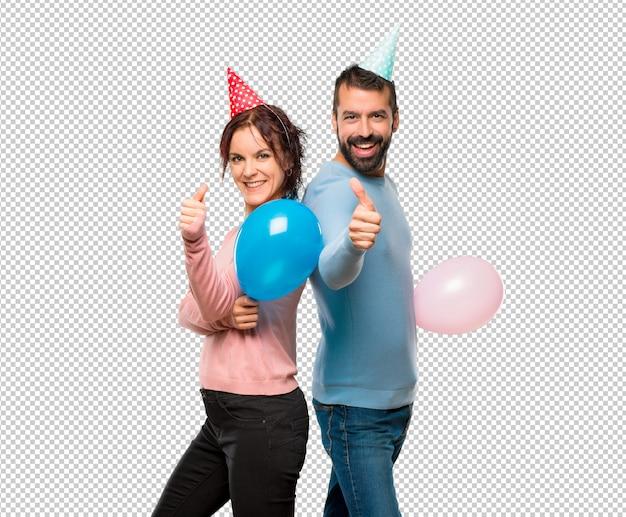 Paare mit den ballonen und geburtstagshüten, die daumen geben, up geste und das lächeln