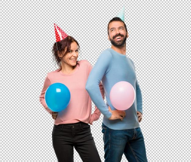 Paare mit den ballonen und geburtstagshüten, die mit den armen an der hüfte und am lachen aufwerfen